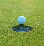 A Golf Ball Nears the Hole. A white golf ball just about to fall into the hole at the end of the course stock image