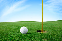 Golf ball next hole. Golf ball on green grass next hole Royalty Free Stock Photo