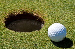 Golf ball next to a hole. On a golf course Royalty Free Stock Image