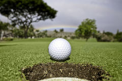 Golf ball next to the hole Royalty Free Stock Photo