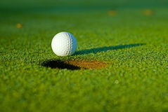 Golf ball on next to hole Stock Photo