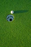 Golf ball on next to hole 4. White golf ball on putting green next to hole with long shadow - from top side down royalty free stock photography