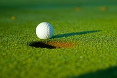 Golf ball on next to hole 5. White golf ball on putting green next to hole with long shadow and selective focus on ball stock images
