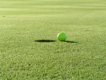Golf ball next to hole. Golf ball on the green next to the hole Stock Image