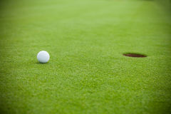 Golf ball next to hole Royalty Free Stock Photos