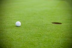 Golf ball next to hole Royalty Free Stock Photos