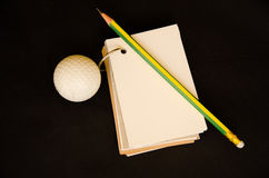 Golf ball with notebook score card Royalty Free Stock Image