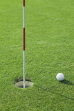 Golf ball and one hole on green Royalty Free Stock Images