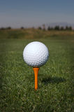 Golf ball on a orange tee Stock Photo