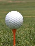 Golf Ball on Orange Tee. A golf ball is teed up on an orange tee Stock Photo