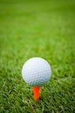 Golf ball. On orange tee on green field Royalty Free Stock Image