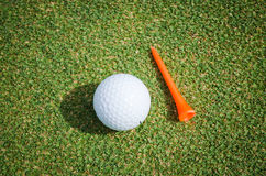 Golf ball and orange tee. Golf ball with orange tee on green grass Stock Images