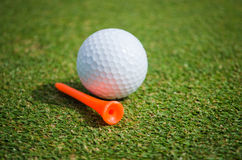 Golf ball with orange tee on green grass. Close up of golf ball with orange tee on green grass Stock Photography