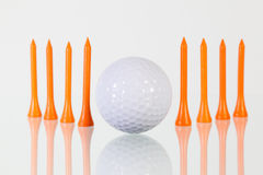 Golf ball and orange tees on the glass table. Golf ball and orange tees on the glass desk Royalty Free Stock Photos
