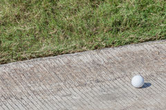 Golf ball out of fairway is near the cement pathway. Stock Images