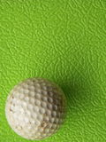 Golf ball past usage. On rough green background Royalty Free Stock Photos