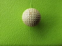 Golf ball past usage. On rough green background Stock Image
