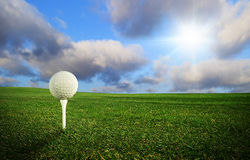 Golf ball in perfect scenery. Golf ball on the tee - idyllic golf course Royalty Free Stock Images