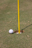 Golf Ball and Pin. At the edge of a golf hole Royalty Free Stock Photo