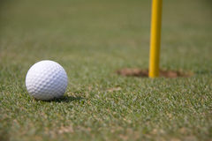 Golf Ball and Pin. A golf course hole in the side Stock Photography