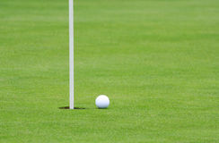 Golf Ball and Pin. Golf ball on the green, near the pin.  Shallow focus Stock Photos