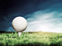 Golf ball placed on white golf tee. On green grass golf course. Moody sunny sky stock photo