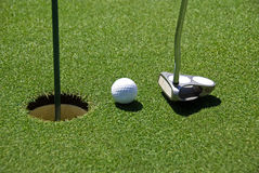 Golf ball on practice hole. Golf ball and drive on practice hole, real golf course Royalty Free Stock Images