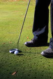 Golf ball and putter. On a green Stock Images