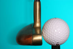 Golf ball and putter. Putter hitting the ball Stock Image