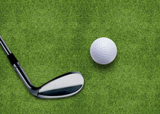 Golf ball and putter. On green grass Royalty Free Stock Photography