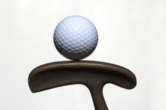 Golf ball and putter. A golf ball balanced on a putter shot against a white background stock image