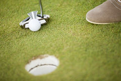 Golf ball, putter and boy's legs on green Royalty Free Stock Images
