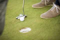 Golf ball, putter and boy's legs on green Stock Photo