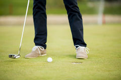 Golf ball, putter and boy's legs on green Royalty Free Stock Photos