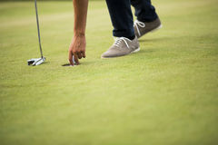Golf ball, putter and boy's legs on green Royalty Free Stock Photo