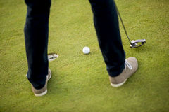 Golf ball, putter and boy's legs on green Royalty Free Stock Photography