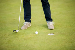 Golf ball, putter and boy's legs on green Stock Images