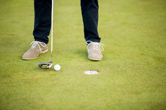 Golf ball, putter and boy's legs on green Stock Photography