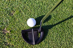 Golf ball and putter club. Close-up of golf ball and putter club Royalty Free Stock Photos