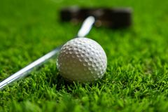 Golf ball and putter on grass royalty free stock photography