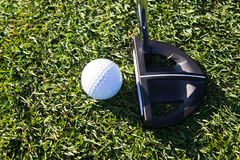 Golf ball and putter on the green Stock Photography