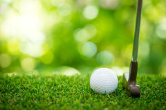 Golf ball and putter. On green Stock Photo