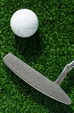 Golf ball and putter on green grass. Background Stock Images