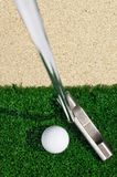 Golf ball and putter on green grass. Outdoor stock photos