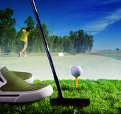 Golf ball and putter on green grass of course against young man Royalty Free Stock Image