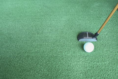 Golf ball and putter on green grass. Sport driving range Stock Images