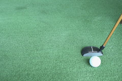 Golf ball and putter on green grass. Sport driving range Stock Photography