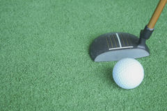 Golf ball and putter on green grass. Sport driving range Royalty Free Stock Photo