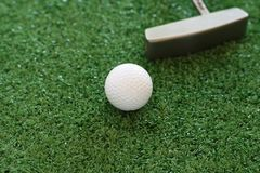Golf ball and putter on green lawn background stock photo