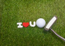Golf ball and putter with I love you sign on green course. Golf ball and putter with I love you wooden sign are on green grass Stock Photography